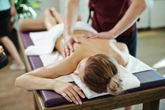 Young Woman Enjoying Massage. Portrait of  young women lying on massage table with eyes closed  blissfully enjoying SPA treatment, men massaging her with lotions Stock Photography