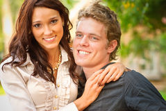 Portrait young women and men. Young beautiful girl smiles and embraces young groom Stock Photos