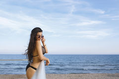 Portrait of a young women with perfect body posing while resting after swimming in the sea in sunny day, Stock Photos