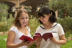 Portrait of young women reading a book at campus. Group of college students looking at the books Royalty Free Stock Photo