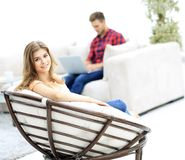 Portrait of young woman sitting in a large comfortable chair. Stock Photography
