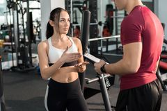 Pretty Young Woman Talking to Fitness Coach royalty free stock photos