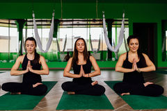Portrait young women three friends in the lotus position on the mat after antigravity yoga exercises. Aerial aero fly Stock Photo