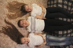 Portrait of young woman and two female teenagers lying on the floor at home, their feet on the couch royalty free stock images