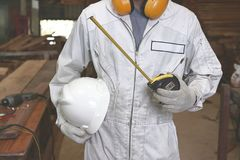 Portrait of young wood worker in white uniform holding safety helmet and measuring tape in carpentry workshop. Stock Photo