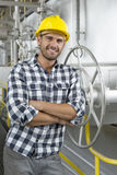 Portrait of young worker with arms crossed leaning on large valve in industry Royalty Free Stock Photography