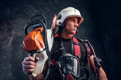 Portrait of young worker with chainsaw and respirator stock image