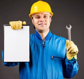 Portrait of a young worker holding a blank clipboard and a wrenc Royalty Free Stock Photography