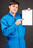 Portrait of young worker holding a pen and a blank clipboard Royalty Free Stock Image
