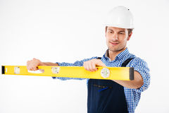 Portrait of a young worker in overalls using level tool Stock Images