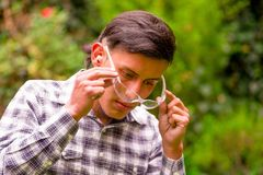 Portrait of young worker wearing transparent safety glasses, long sleeve shirt and ear plugs to protect from noise, in a. Blurred nature background Royalty Free Stock Photography