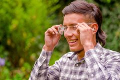 Portrait of young worker wearing transparent safety glasses, long sleeve shirt and ear plugs to protect from noise, in a. Blurred nature background Stock Photos