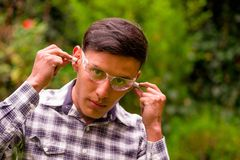 Portrait of young worker wearing transparent safety glasses, and wearing a long sleeve shirt, putting ear plugs to. Protect from noise, in a blurred nature Royalty Free Stock Photography