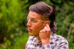 Portrait of young worker wearing transparent safety glasses, and wearing a long sleeve shirt, putting ear plugs to. Protect from noise, in a blurred nature Stock Image