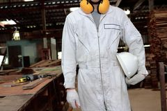 Portrait of young worker in white uniform holding safety helmet in carpentry workshop. Stock Image
