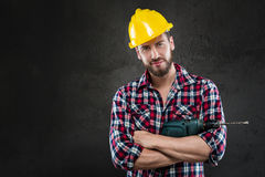 Portrait of young workman with drill. Portrait of Attractive bearded workman in chequed shirt and helmet, standing with crossed arms and drill, looking at camera Royalty Free Stock Photos