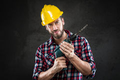 Portrait of young workman with drill. Portrait of attractive confident bearded workman with chequed shirt and yellow helmet, standing holding a drill, looking at Royalty Free Stock Photos