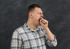 Portrait of young yawning man. Sleepy guy gape and close his mouth with hand, gray studio background Stock Images