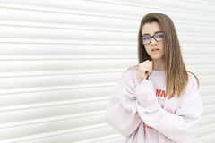 Portrait of a young 15 year old teenager. With glasses on a metallic background. Horizontal shot Stock Photo