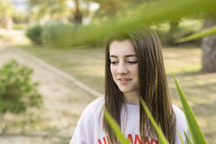 Portrait of a young 15 year old teenager. Between the plants of a park Royalty Free Stock Photos