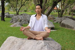 Portrait of young yogi man in white shirt doing yoga meditation while sitting in lotus position on the rock in beautiful outdoor p. Ark Royalty Free Stock Photos