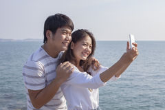 Portrait of younger asian man and woman taking a photograph by s Royalty Free Stock Photo