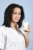 Portrait of youth female with milk. Youth female standing in profile and holding a glass with milk on blue background,check also my collection Healthy life Stock Photo