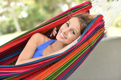 Portrait of yung woman lying in hammock and relaxing. Portrait of smiling girl relaxing in hammock Stock Images