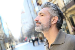 Portrait of zen mature man in city. Portrait of serene mature man in town royalty free stock photo