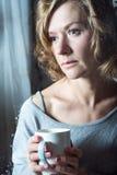 Portraite de la mujer joven con la taza Foto de archivo