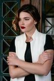 Portraite dei giovani, bella donna triste con brevi capelli marroni con alla moda compone in vestito nero e panciotto bianco Fotografia Stock