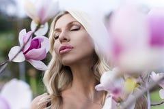 Portraitfrau mit Blumenmagnolie Stockbild