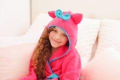 Portraiti des schönen gelockten Mädchens, das ein rosa bathtowel mit Haube trägt stockfoto