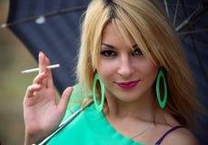 Portraitmädchen mit Regenschirm und Zigarette Lizenzfreie Stockfotografie