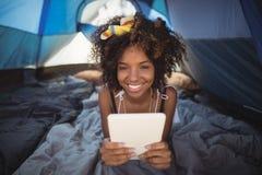 Portraitn счастливой женщины используя цифровую таблетку пока лежащ вниз в шатре Стоковая Фотография