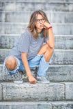 Portraito av unga flickan i en fri modern dräkt från jeans med hål royaltyfri foto