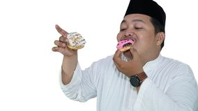 Portraits of Asian Muslim men who are overweight enjoy eating two donuts with pleasure royalty free stock photography