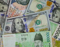 Portraits on banknotes. Stack of may banknotes. US dollars, Korea won bills. Close up Stock Photos