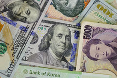 Portraits on banknotes. Stack of may banknotes. US dollars, Korea won bills and Japan yen. Close up Stock Photography