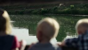 Portraits of children seating on the bridge and looking at the river in summer park Full HD