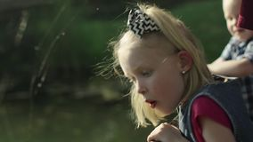 Portraits of children seating on the bridge and looking at the river in summer park slow motion Full HD