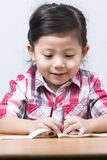 Portraits Cute Asian Girl playing on wooden table. While intending to assemble toy parts Royalty Free Stock Photos