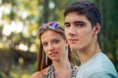 Portraits de beaux type et fille enamourés La fille avec des verres sur la tête se tient à côté de l'ami Photographie stock libre de droits