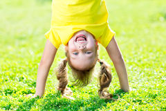 Portraits of happy kid playing upside down outdoors in summertime standing on hands on grass Stock Photography
