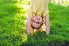 Portraits of happy kids playing upside down outdoors in summer p. Ark walking on hands Royalty Free Stock Images
