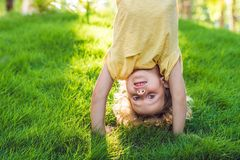 Portraits of happy kids playing upside down outdoors in summer park walking on hands.  Stock Image