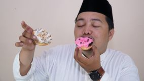 Portraits of Asian Muslim men who are overweight enjoy eating two donuts with pleasure