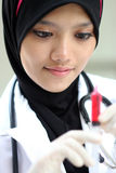 A portraits of pretty muslim woman doctor. Checking syringe stock images