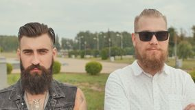 Portraits of three brutal bearded young men on the street.