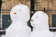 Portraits of two snowmen in the park Royalty Free Stock Photos